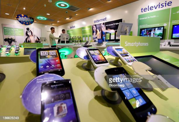 A selection of smartphones sit on display inside a Royal KPN NV store as customers browse mobile phone tariffs on a computer screen in The Hague...