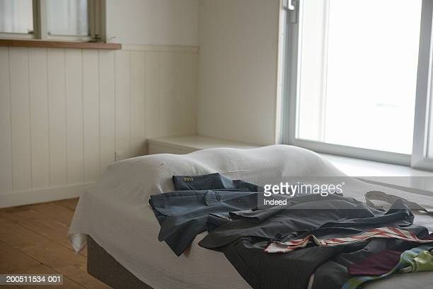 Selection of suits laid out on double bed in bedroom