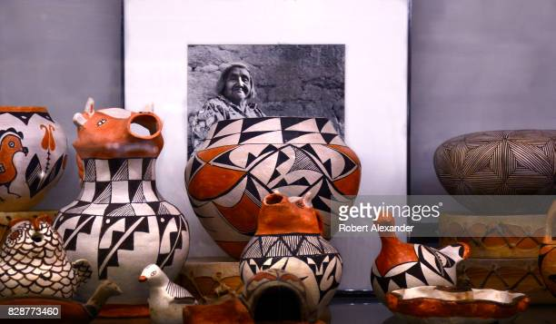 A selection of traditional Native American pottery for sale in a shop in Santa Fe New Mexico displayed with a photograph of famed Acoma Pueblo potter...