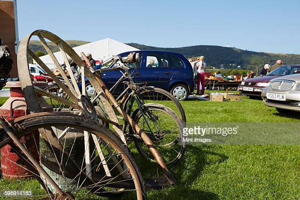 Selection of vintage bicycles, wheel rim and an old milk churn for sale at a flea market event.