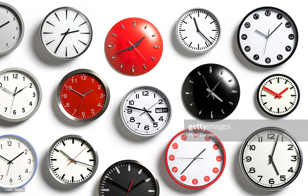 A selection of wall clocks showing different times : Stock Photo