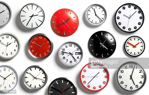 a selection of wall clocks showing different times - wall clock stock photos and pictures