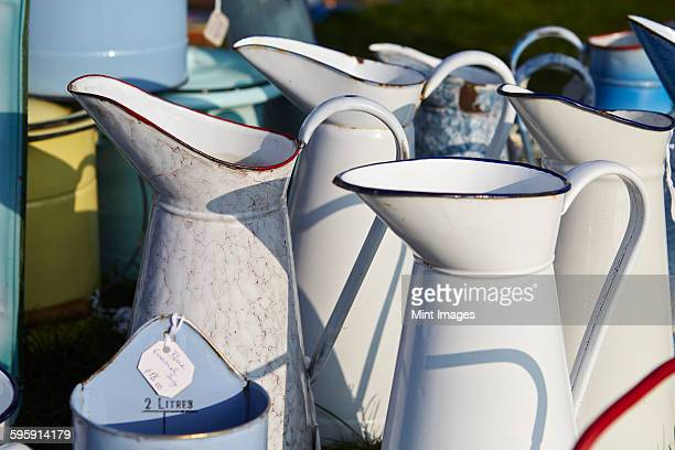 Selection of white vintage enamel jugs for sale.