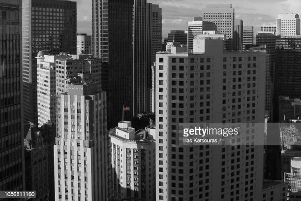 selective coloring of american flag flying among skyscrapers in san francisco - san francisco financial district stock pictures, royalty-free photos & images