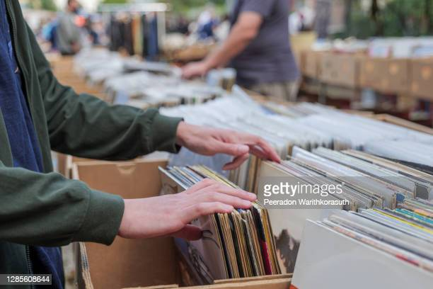 selective focus at hand which pick and select second hand old fashion phonograph discs  in the paper box at the stall in open air flee market in berlin, germany. - record analog audio stock pictures, royalty-free photos & images