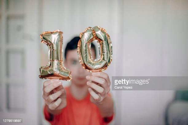selective focus boy holding golden 10 air balloon - 10 11 jahre stock-fotos und bilder