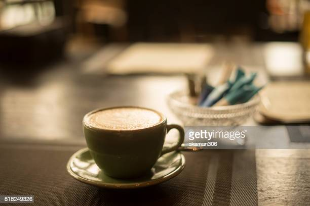 selective focus coffee with Artist determinant start up working with smart-phone on work space and soft flare filter