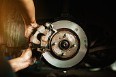 Selective focus disc brake on car, in process of new tire replacement,Car brake repairing in garage