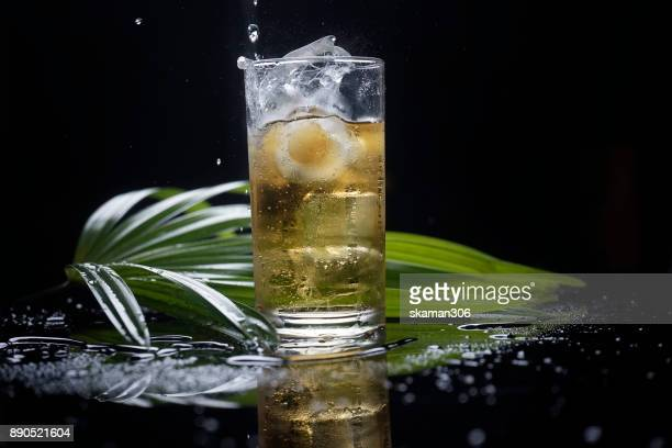 selective focus drink alcohol and water glass with dark rum whisky and Sparking water and ice cube