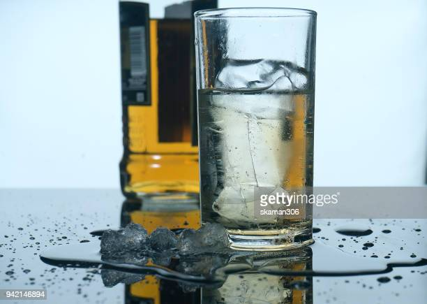 selective focus drink alcohol and water glass with whisky and Sparking water and ice cube