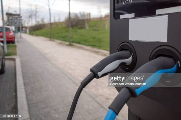 selective focus, ev electric vehicle changing station on sidewalk beside car park on street in germany. - north rhine westphalia stock pictures, royalty-free photos & images