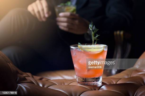 selective focus  glass of cocktail with business guy holding drinks - cocktail stock-fotos und bilder