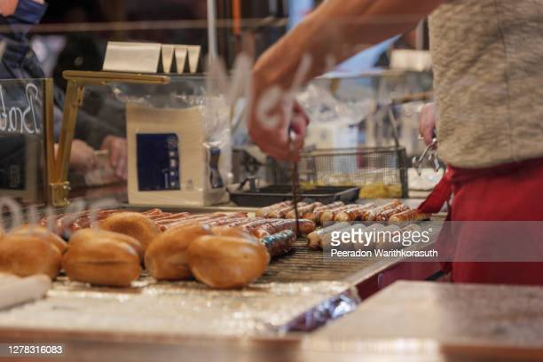 selective focus, heap of grilling sausages on barbecue grill beside brötchen, german style bread, at a stall of christmas market in winter season in germany. - evening meal imagens e fotografias de stock