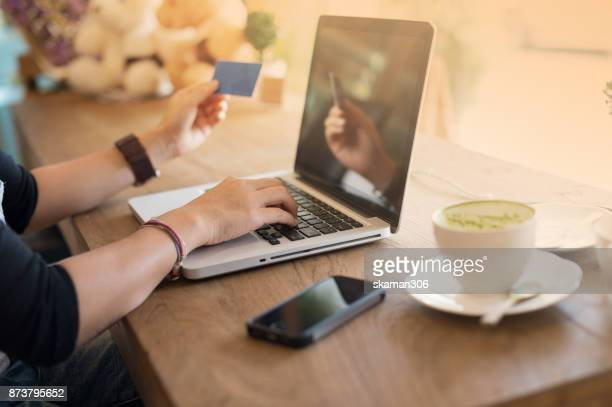 selective focus hipster female hand  shopping & paying online market by smartphone with laptop computer