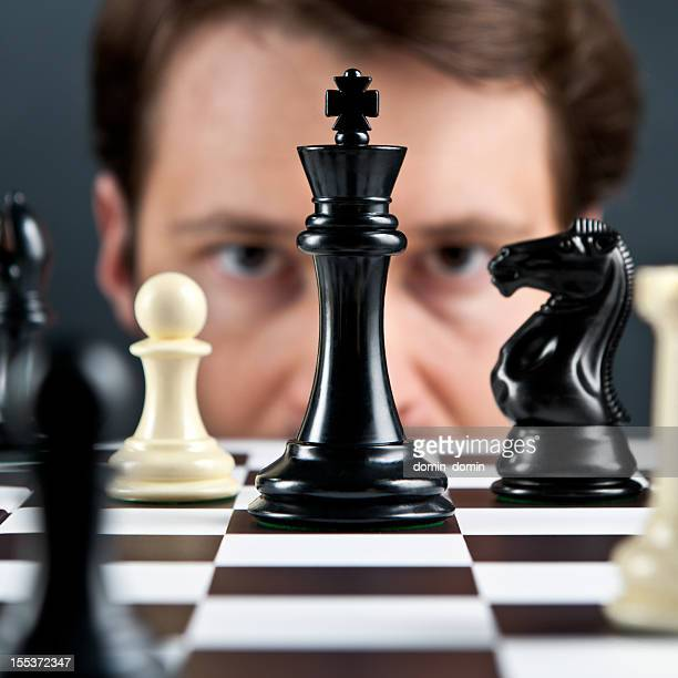 Selective focus, man's eyes on chess pieces
