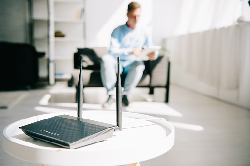 selective focus of black plugged router on white table and businessman sitting on sofa 1182451034