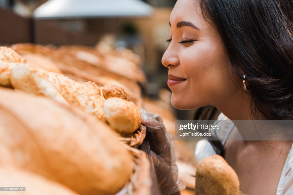 selective focus of cheerful asian woman smiling while smelling bread in supermarket : Stock Photo