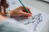 selective focus of illustrator drawing cartoon character on paper