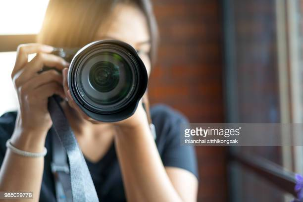 selective focus of lady looking viewfinder in camera - photographic equipment stock pictures, royalty-free photos & images