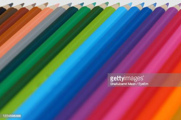 selective focus of pencil colours on near-white chopping board - shaifulzamri stock pictures, royalty-free photos & images