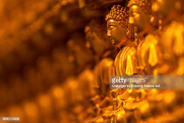 Selective focus of the golden buddha statue in a row.