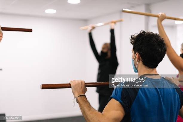 selective focus on the back of a man wearing a mask doing fitness exercises with a wooden stick in a class led by a trainer in a gym - turner syndrome stock-fotos und bilder