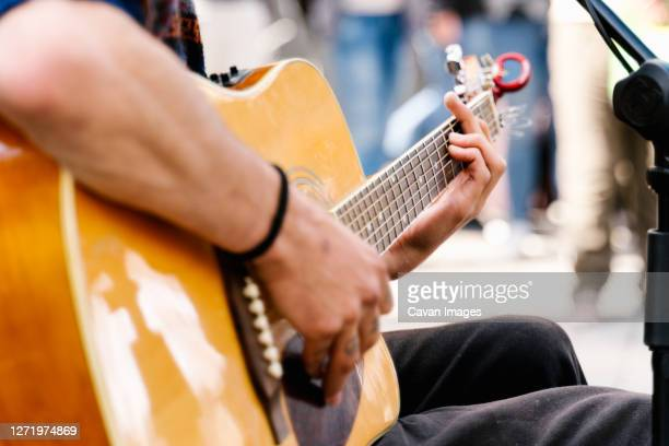 selective focus on the hands of a young man playing a guitar in a crowded street - musician stock pictures, royalty-free photos & images