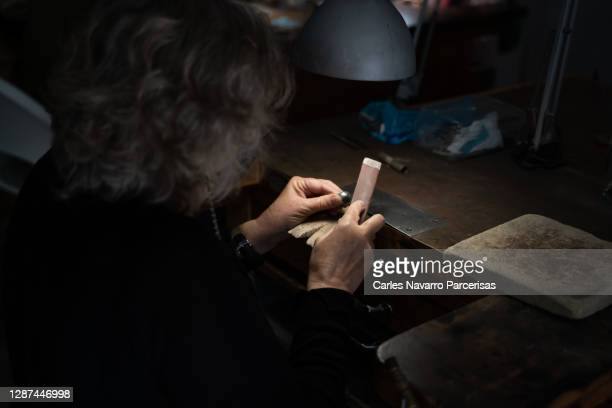 selective focus on the hands of an elderly woman working in a jewelry workshop sanding a silver ball - artists equity ball stock pictures, royalty-free photos & images