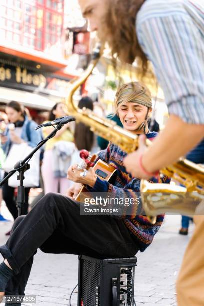 selective focus ont he face of a man singing while playing guitar next to a saxophonist in the street - musician stock pictures, royalty-free photos & images