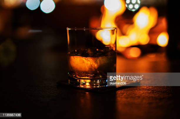 selective focus pure whisky with ice cube inside whisky glass on fire wood background - scotch whiskey stock pictures, royalty-free photos & images
