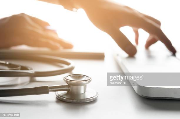 Selective focus Stethoscope and Doctor working an tablet on desk in hospital, Healthcare and medical concept
