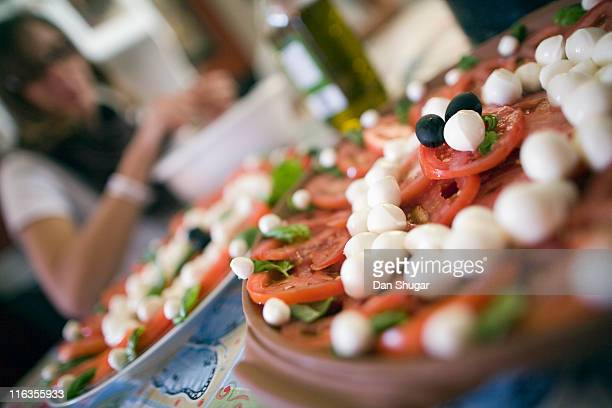Selective focus view of a woman preparing plates of sliced tomato, fresh organic basil and balls of fresh mozzarella (bocconcini).
