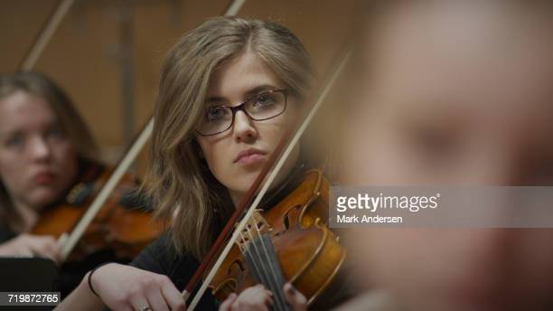 selective focus view of serious teenage girl musician playing violin in band class - girl band stock pictures, royalty-free photos & images