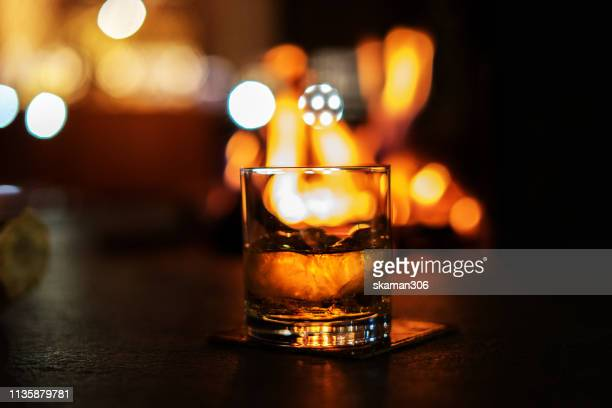 selective focus whiskey glass with bonfire - whiskey stock pictures, royalty-free photos & images