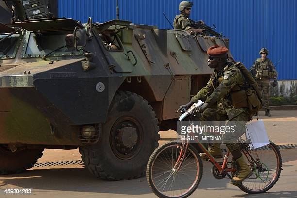 A Seleka soldier rides a bicycle past French troops part the of Sangaris operation patrolling in the PK 0 district of Bangui on December 25 2013...