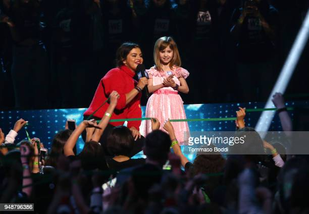Selena Gomez and youth advocate Nellie Mainor speak onstage at WE Day California at The Forum on April 19 2018 in Inglewood California
