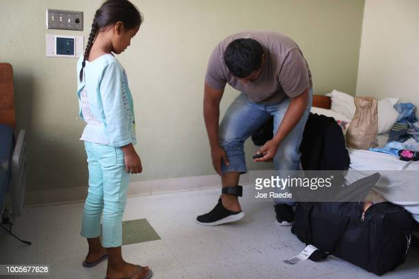 Selena watches as her father Luis works on changing the battery in his ankle monitor as they are cared for in an Annunciation House facility after...