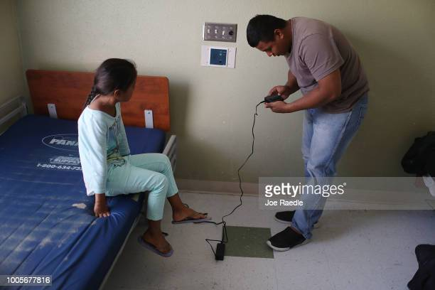 Selena watches as her father Luis works on charging his ankle monitor battery as they are cared for in an Annunciation House facility after they were...