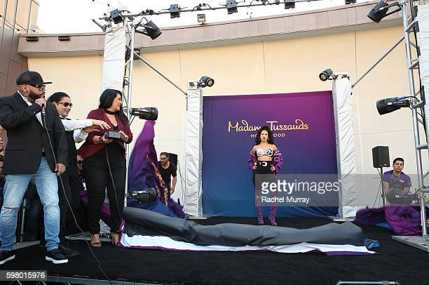 Selena's brother A.B. Quintanilla, husband Chris Perez, and sister Suzette Quintanilla drop the curtain onstage during Madame Tussauds Hollywood's...