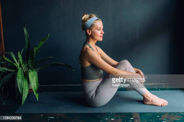 self care rituals: beautiful fit blonde woman doing yoga at home - hair band stock pictures, royalty-free photos & images