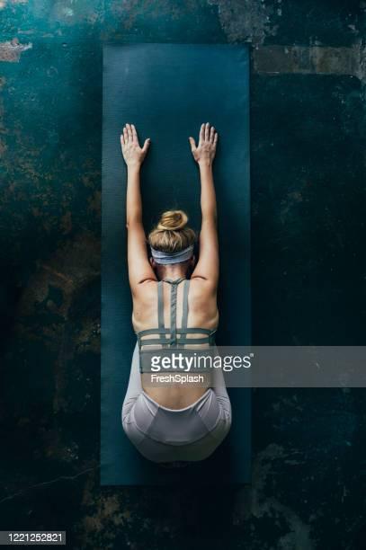 rituali di cura di sé: donna bionda che fa yoga a casa, una vista aerea - vita attiva foto e immagini stock