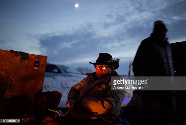A self described water protector stays warm by a fire at the Oceti Sakowin camp Just outside of the Lakota Sioux reservation of Standing Rock North...