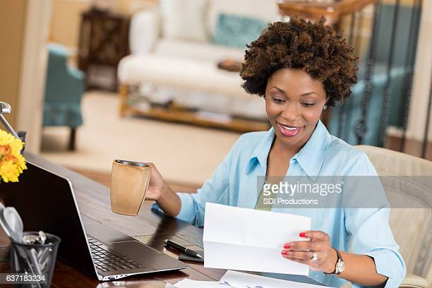 Self employed woman reads her mail in home office