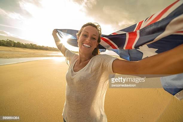 Self portrait of caucasian female holding Australian flag on beach