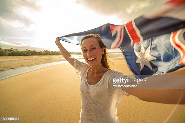 Self portrait of caucasian female holding Australian flag on beach