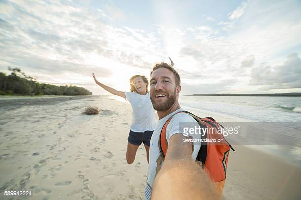 Self portrait of playful young couple on beach at sunset