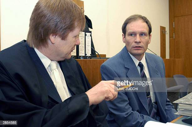 Self-confessed German cannibal Armin Meiwes speaks to his lawyer Harald Ermel at the beginning of a session in a Kassel court, 09 January 2004....