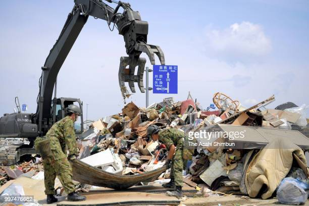SelfDefense Force members clear the debris from a temporary collection point on July 13 2018 in Kurashiki Okayama Japan The death toll from the...