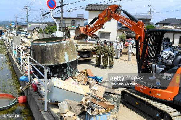SelfDefense Force members use a heavy machine to remove debris on July 13 2018 in Kurashiki Okayama Japan The death toll from the torrential rain in...