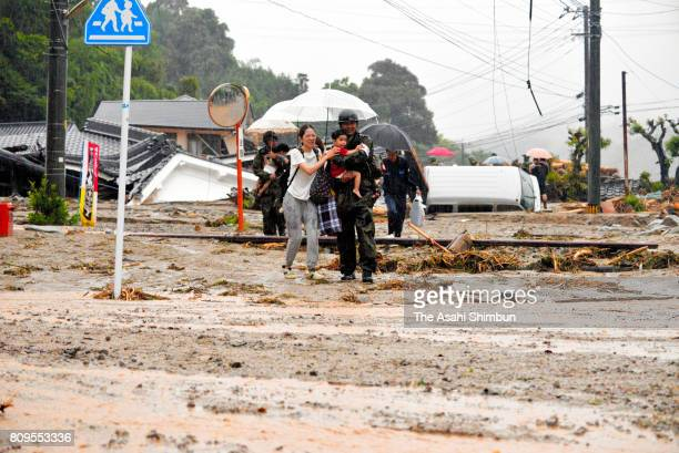 SelfDefense Forces members help residents evacuate on a road covered with driftwood and debris as torrential rain hits on July 6 2017 in Asakura...